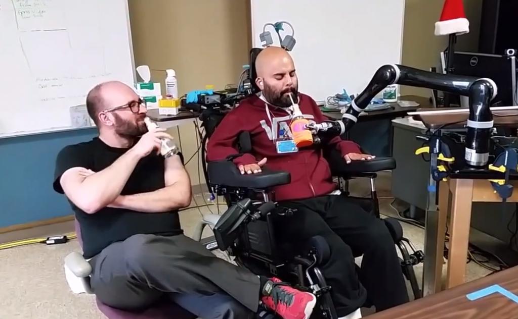 Een verlamde man drinkt met behulp van een robot, die direct wordt aangestuurd via zijn gedachten. Bron: youtube